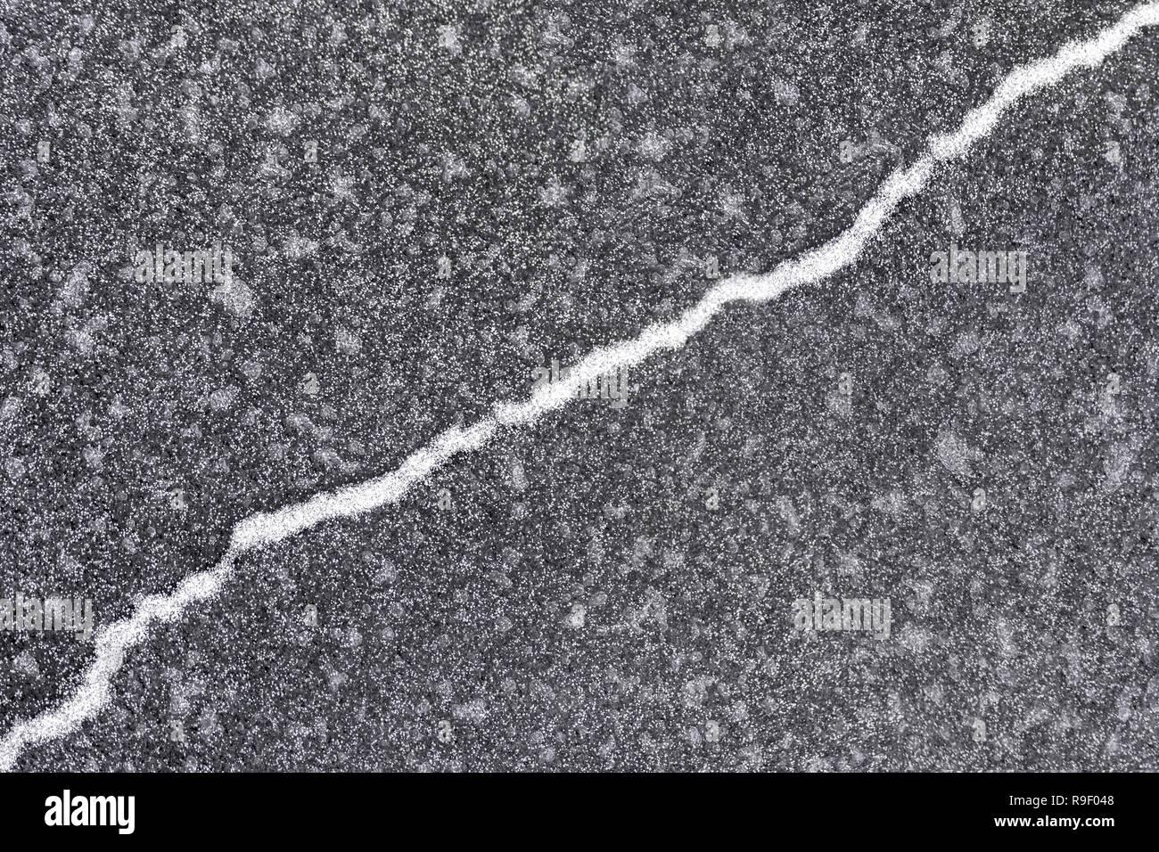 Den Riss auf der grauen Eis in Pulverform mit Schnee und läuft schräg nach oben. Stockfoto