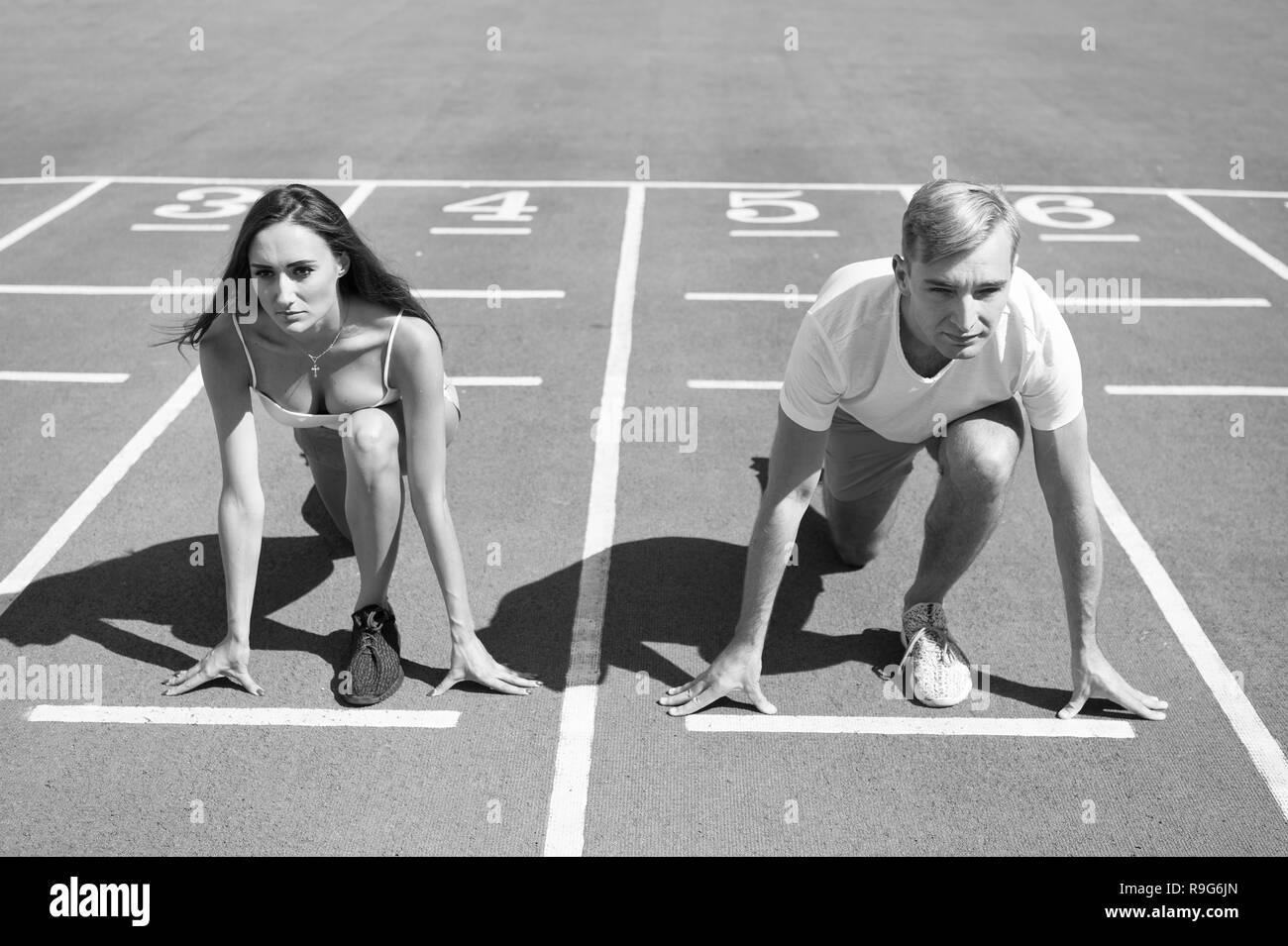 Gleichen Kräften Konzept. Mann und Frau niedrigen Startposition Lauffläche Stadion. Läuft der Wettbewerb Geschlecht oder Rasse. Schneller Sportler erzielen Sieg. Sport Herausforderung für Paare. Jeder hat die Chance. Stockbild