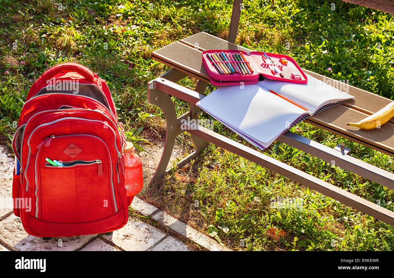 Modernes rotes Schultasche und Bleistift Box mit Notebook auf der Bank auf dem Schulhof Stockfoto