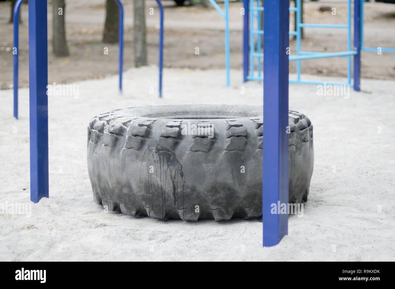 Klettergerüst Reifen : Eine große schwarze reifen gegen straße sportplatz zum