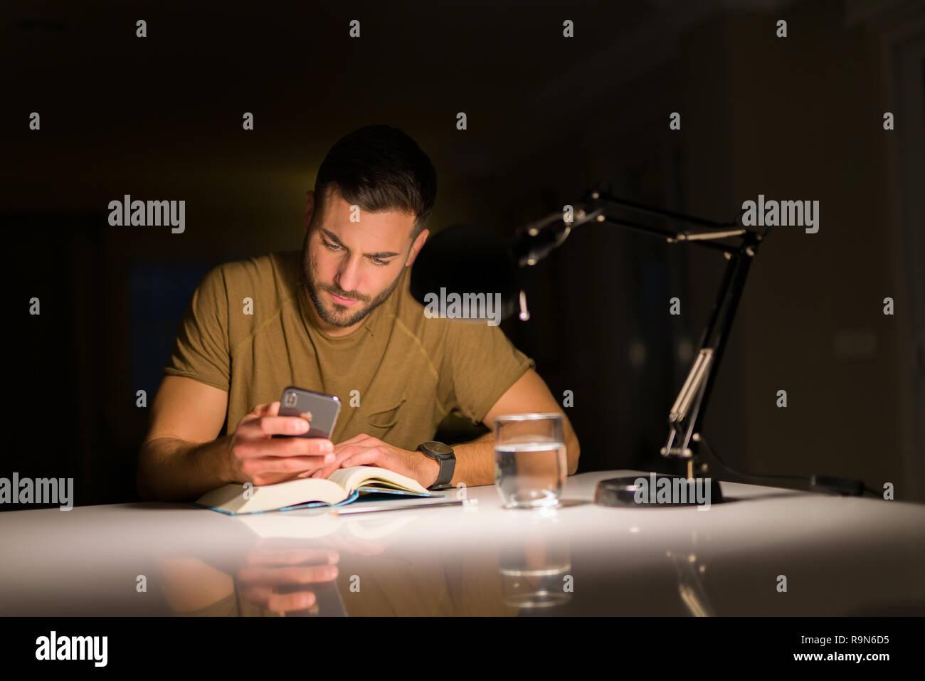 Jungen gutaussehenden Mann zu Hause studieren, mit Smartphone, am Telefon suchen Stockfoto
