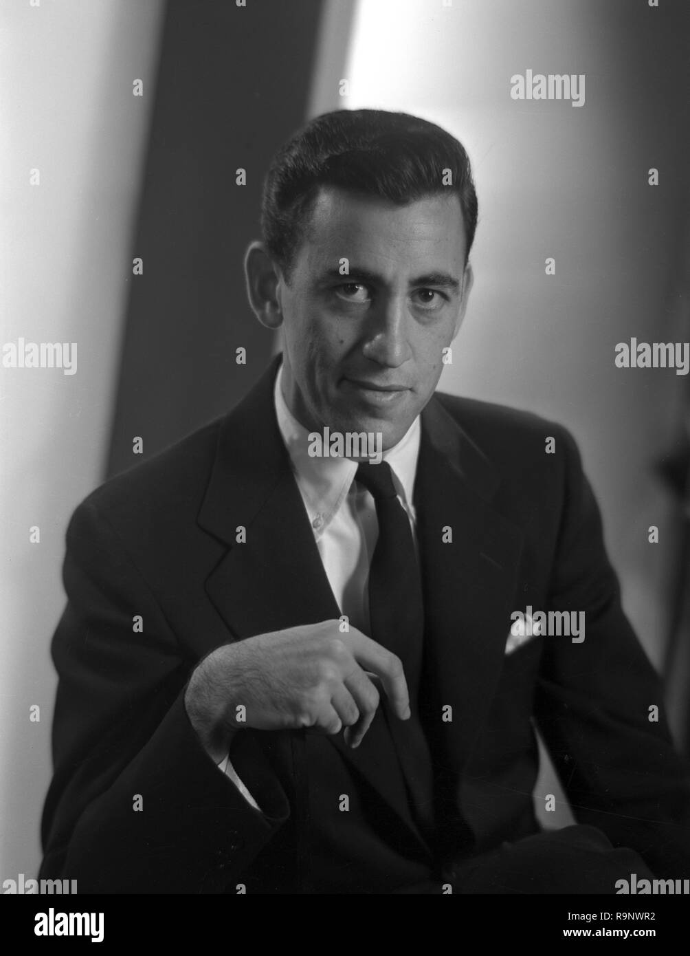 Drei viertel länge sitzt Portrait von Thema Jerome David Salinger (JD Salinger) trägt einen dunklen Anzug und Krawatte und Blick in die Kamera, eine Hand mit Zeigefinger teilweise verlängert, mit einem Hintergrund von Graustufen Licht und Schatten, von Lotte Jacobi in New York City, New York, 1950 fotografiert. () Stockbild