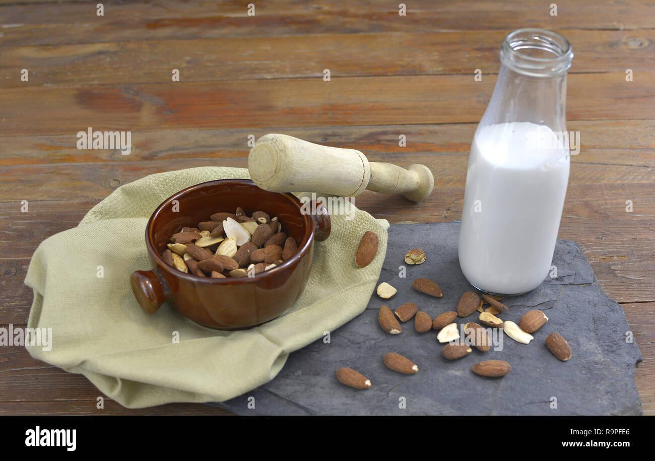 Hausgemachtes Mandel Milch in der Flasche mit Mandeln in eine Schüssel geben. Molkerei alternative Milch - close up mit Platz für Text Stockbild