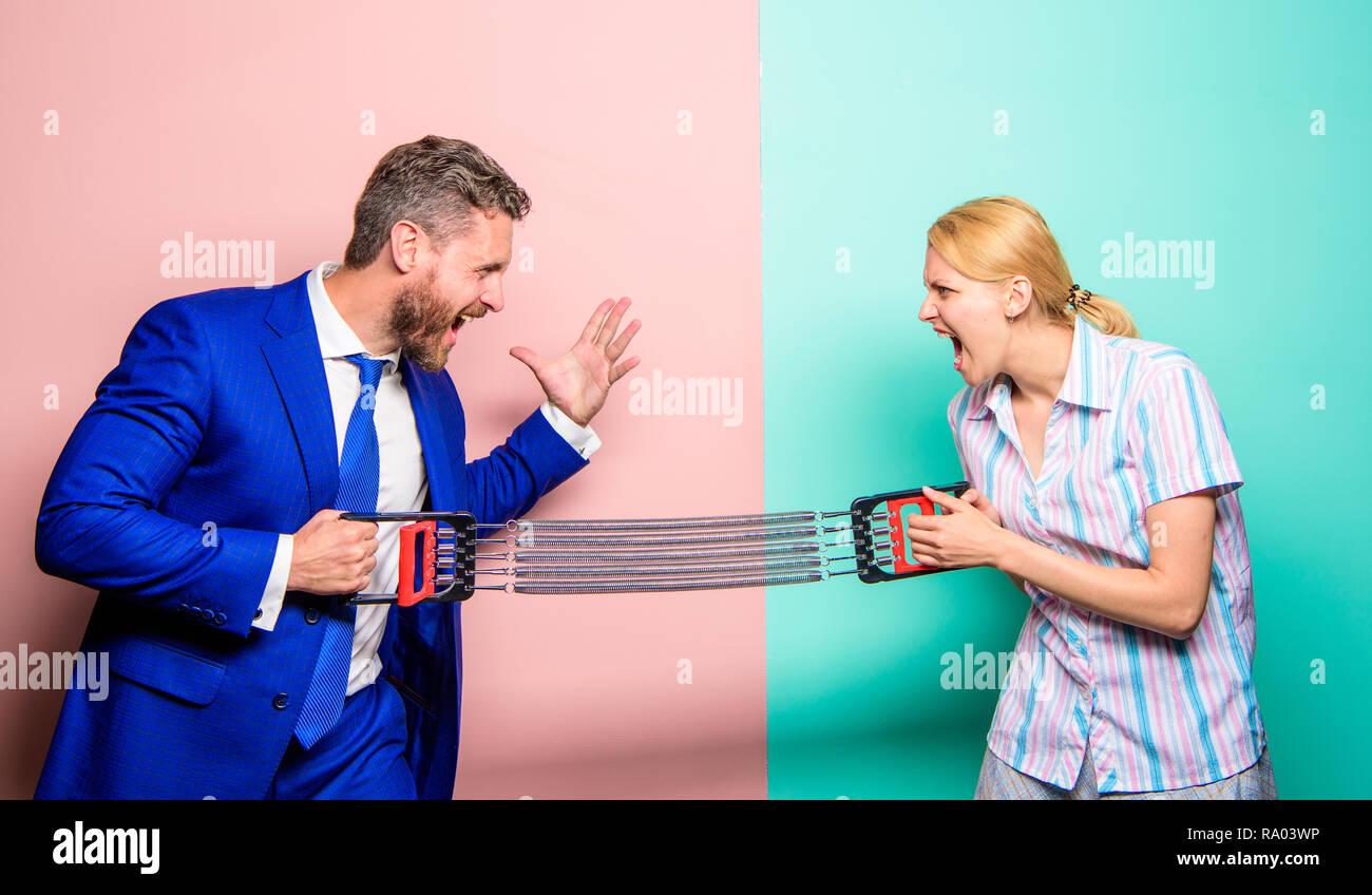 Die Gleichstellung der Geschlechter und Nichtdiskriminierung. Geschlecht Rivalität Konzept. Mann und Frau stretching Expander gegenüberliegenden Seiten. Business Rivalität Kerl und ein Mädchen. Die Konfrontation der Geschlechter am Arbeitsplatz. Geschlecht die gleichen Rechte. Stockbild