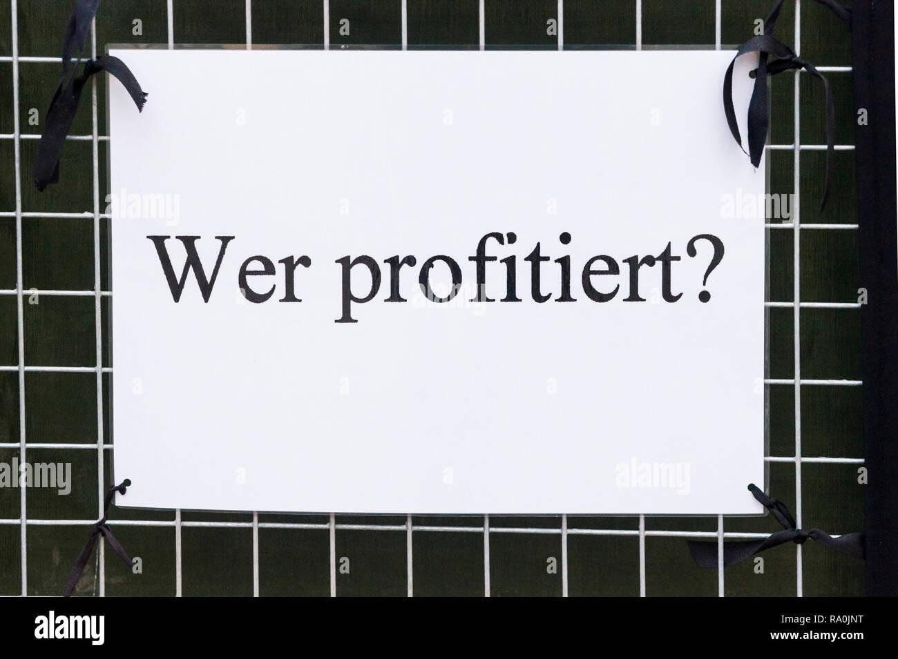 """Poster mit einem Text, der lautet: """"Wer profitiert?"""", Stockbild"""