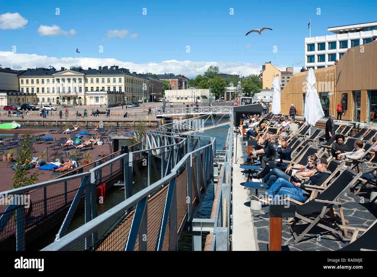 23.06.2018 - Helsinki, Finnland, Europa - Ein Blick auf die Sonnenterrasse des Allas Meer Pool mit Hafen, Marktplatz und dem Praesidentenpalais im Tipp Stockbild