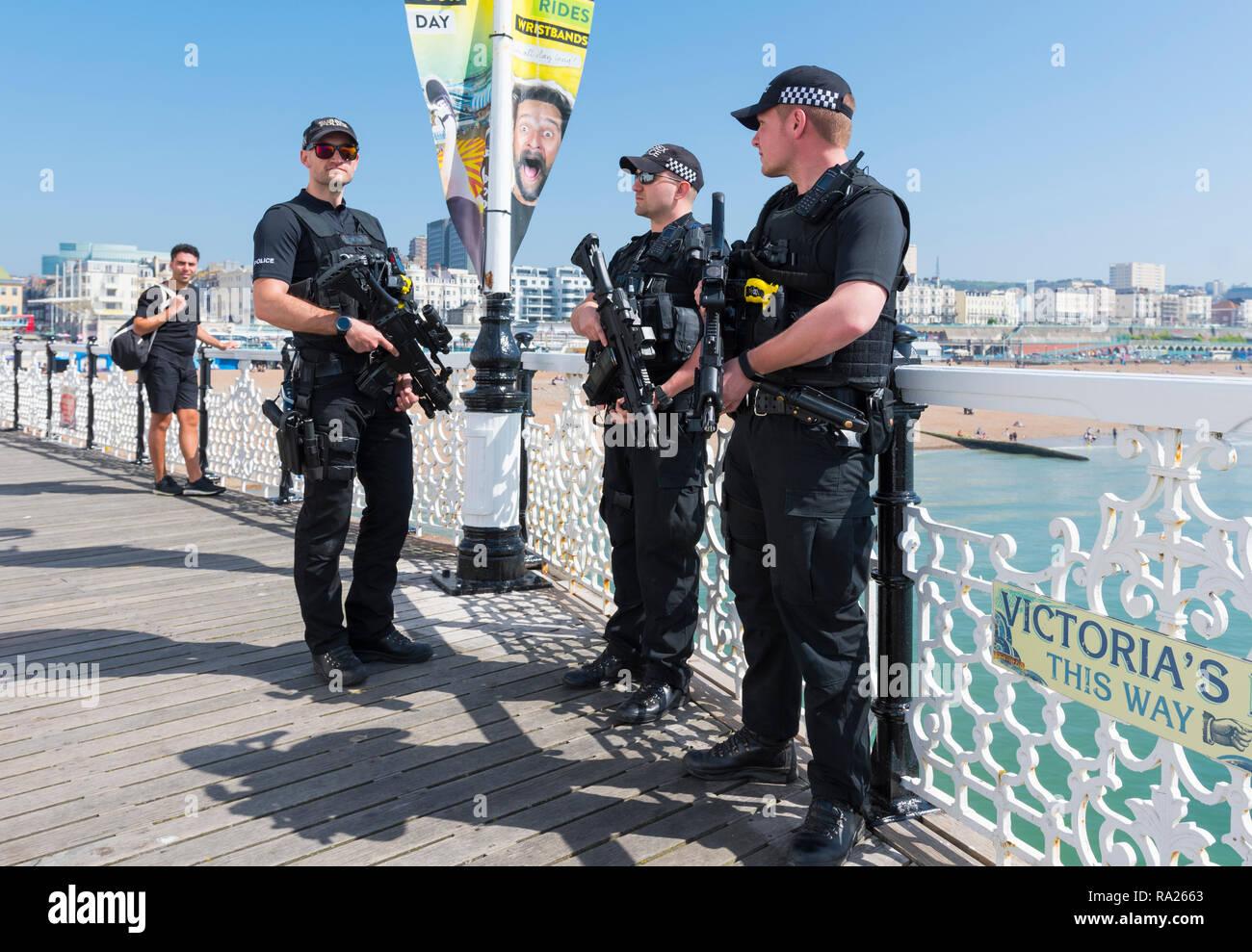Bewaffnete Polizisten patrouillieren Brighton Pier im Frühjahr in Großbritannien. Britische Polizei mit Schusswaffen am Meer. Polizei hinter Gewehren, Großbritannien. Stockbild