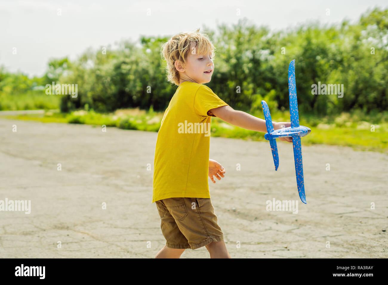 Glückliches Kind spielen mit Spielzeug Flugzeug gegen alte Landebahn Hintergrund. Mit Kindern unterwegs Konzept Stockbild