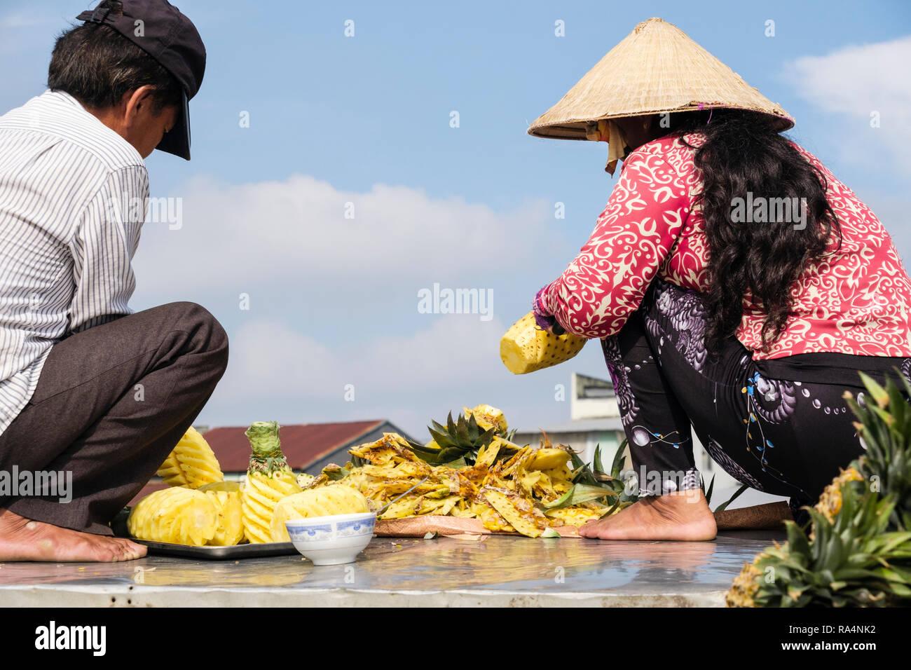 Eine vietnamesische Mann und Frau bereiten Ananas Obst in schwimmenden Markt auf Hau Flusses zu verkaufen. Can Tho, Mekong Delta, Vietnam, Asien Stockbild