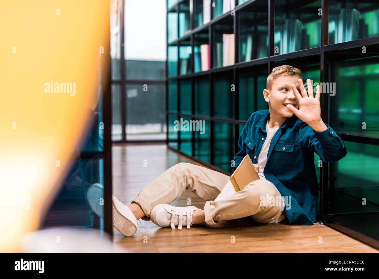Lächelnden Schuljungen holding Buch und winkende Hand beim Sitzen auf dem Boden in der Bibliothek Stockfoto