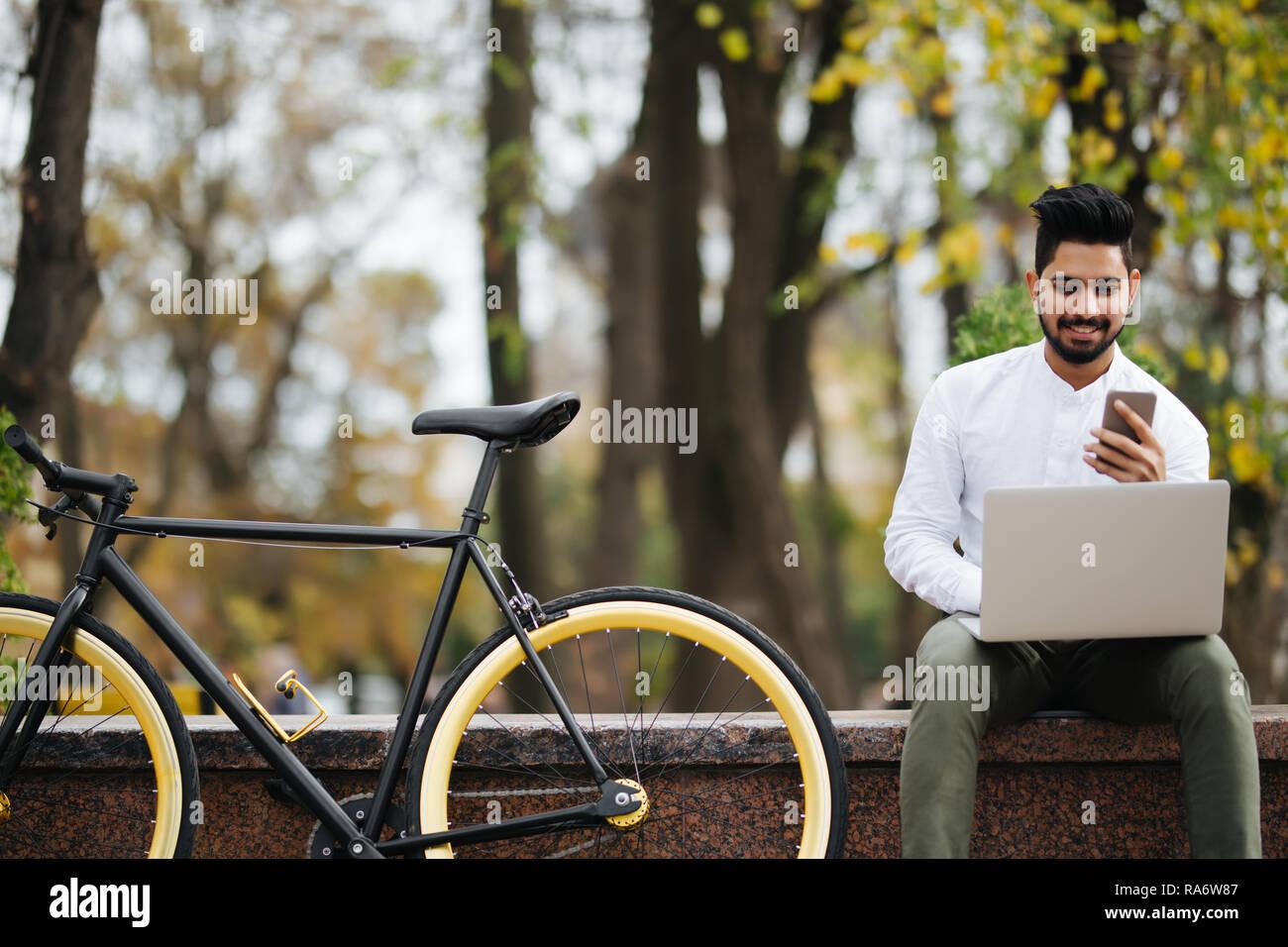 Glückliche junge indische Mann mit Handy während der Arbeit am Laptop sitzen im Freien in der Nähe Fahrradverleih Stockfoto