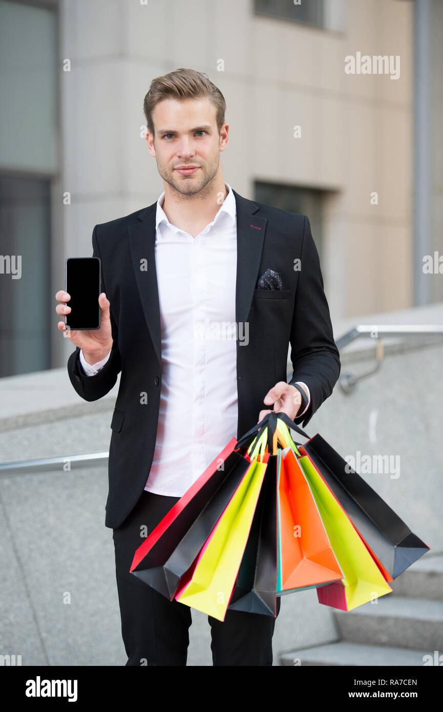 Online einkaufen. Unternehmer nutzen Sie die Anwendung. Der Mensch trägt Einkaufstaschen während Halten Sie Telefon im städtischen Hintergrund. Erfolgreicher Geschäftsmann online einkaufen. Beschäftigte Leute schätzen Online Service. Stockbild