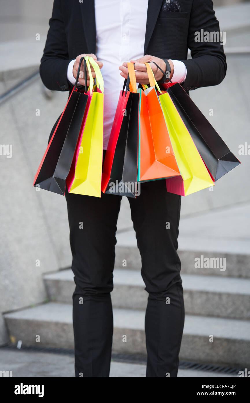 Der Mensch trägt Einkaufstaschen im städtischen Hintergrund. Erfolgreicher Geschäftsmann online einkaufen. Beschäftigte Leute schätzen Online Service. Online einkaufen. Kauf Lieferung. Unternehmer nutzen Sie die Anwendung. Stockbild