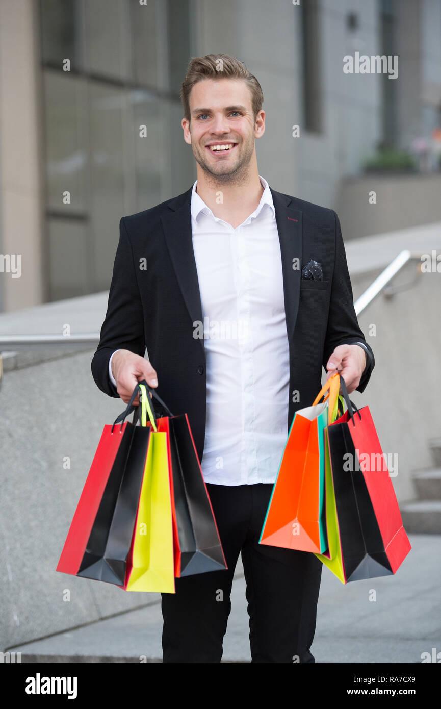 Unternehmer nutzen Sie die Anwendung. Der Mensch trägt Einkaufstaschen im städtischen Hintergrund. Erfolgreicher Geschäftsmann online einkaufen. Beschäftigte Leute schätzen Online Service. Online einkaufen. Kauf Lieferung. Stockbild