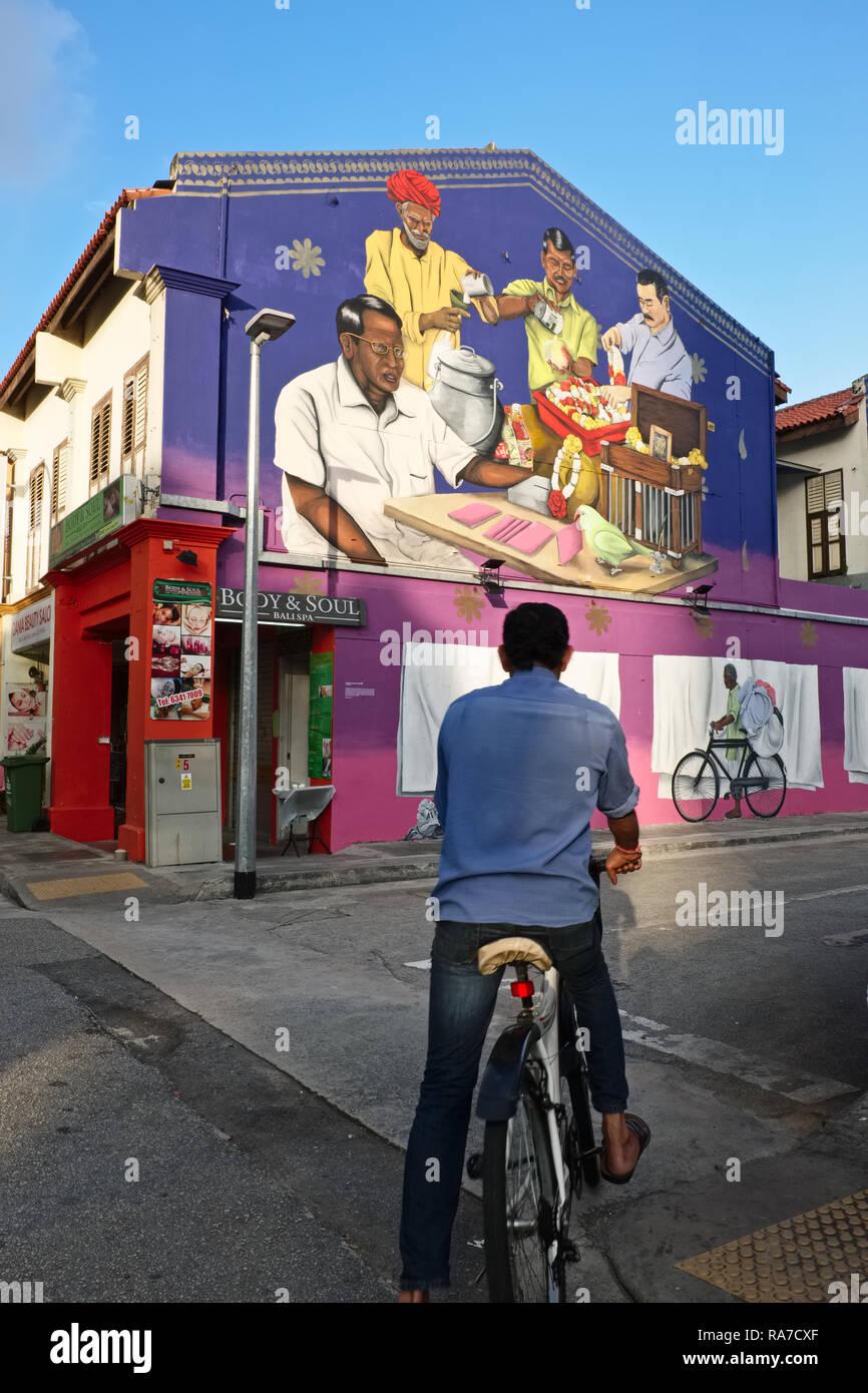 Ein Radfahrer in Little India, Singapur, schaut auf eine Wand Gemälde der Darstellung Berufen der frühen indischen Einwanderer, wie z. B. einem Dhobi mit seinem Fahrrad Stockbild