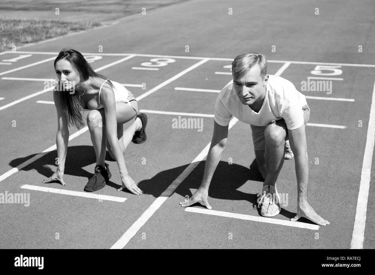Mann und Frau niedrigen Startposition Lauffläche Stadion. Läuft der Wettbewerb Geschlecht oder Rasse. Schneller Sportler erzielen Sieg. Sport Herausforderung für Paare. Jeder hat die Chance. Gleichen Kräften Konzept. Stockbild