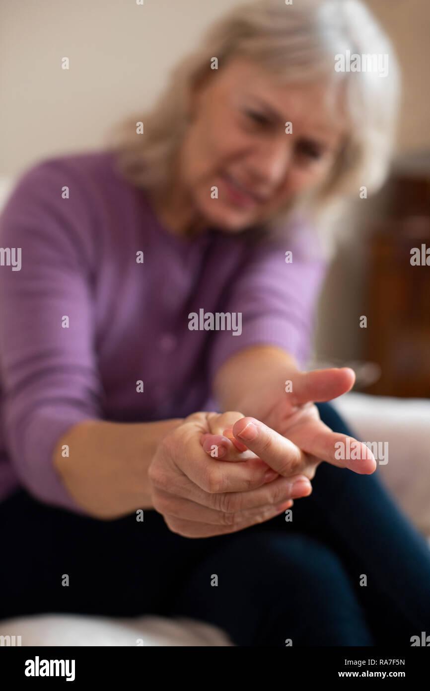 Ältere Frau zu Hause leiden mit Arthritis Stockbild