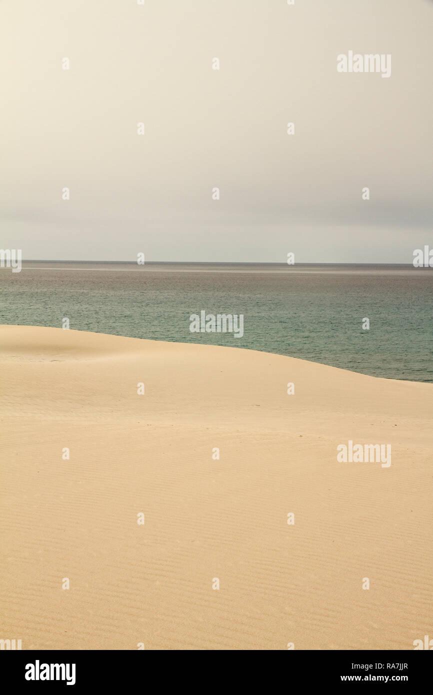Der graue Himmel bricht abrupt auf den Winter Meer harmonisch durch die gelbe Sanddüne gekennzeichnet Stockbild