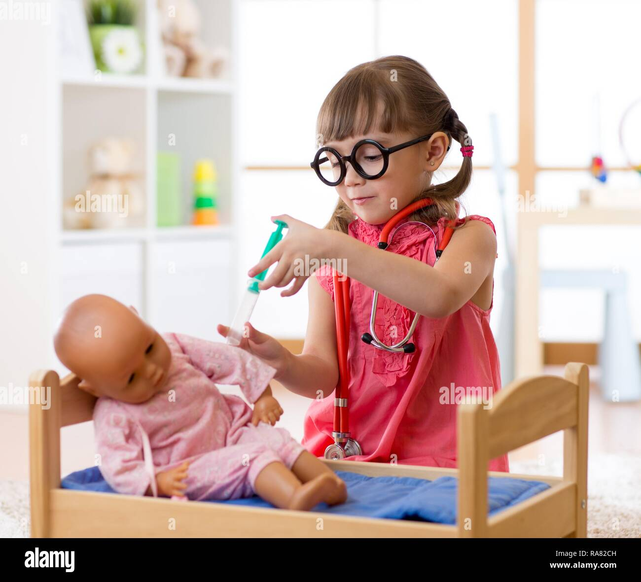 Kind kleine Mädchen spielen mit Spielzeug Puppe in Kindergärten Stockfoto