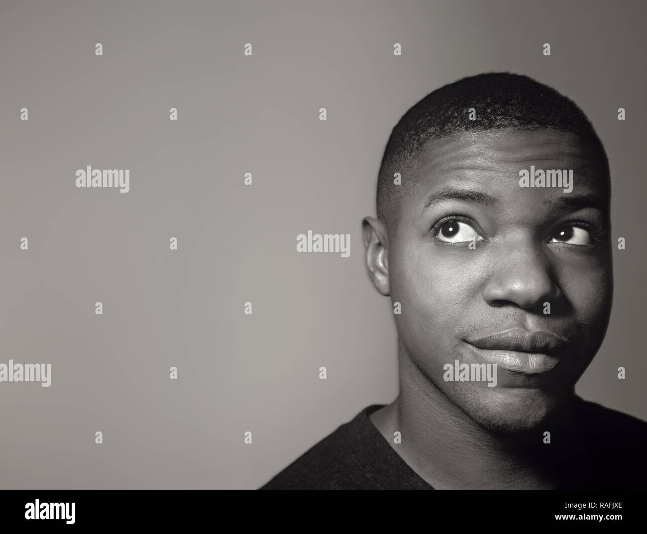 Schwarzer Mann denken über etwas in seinem Geist und seinem Blick nach rechts, der versucht, mit Ideen zu kommen Stockbild