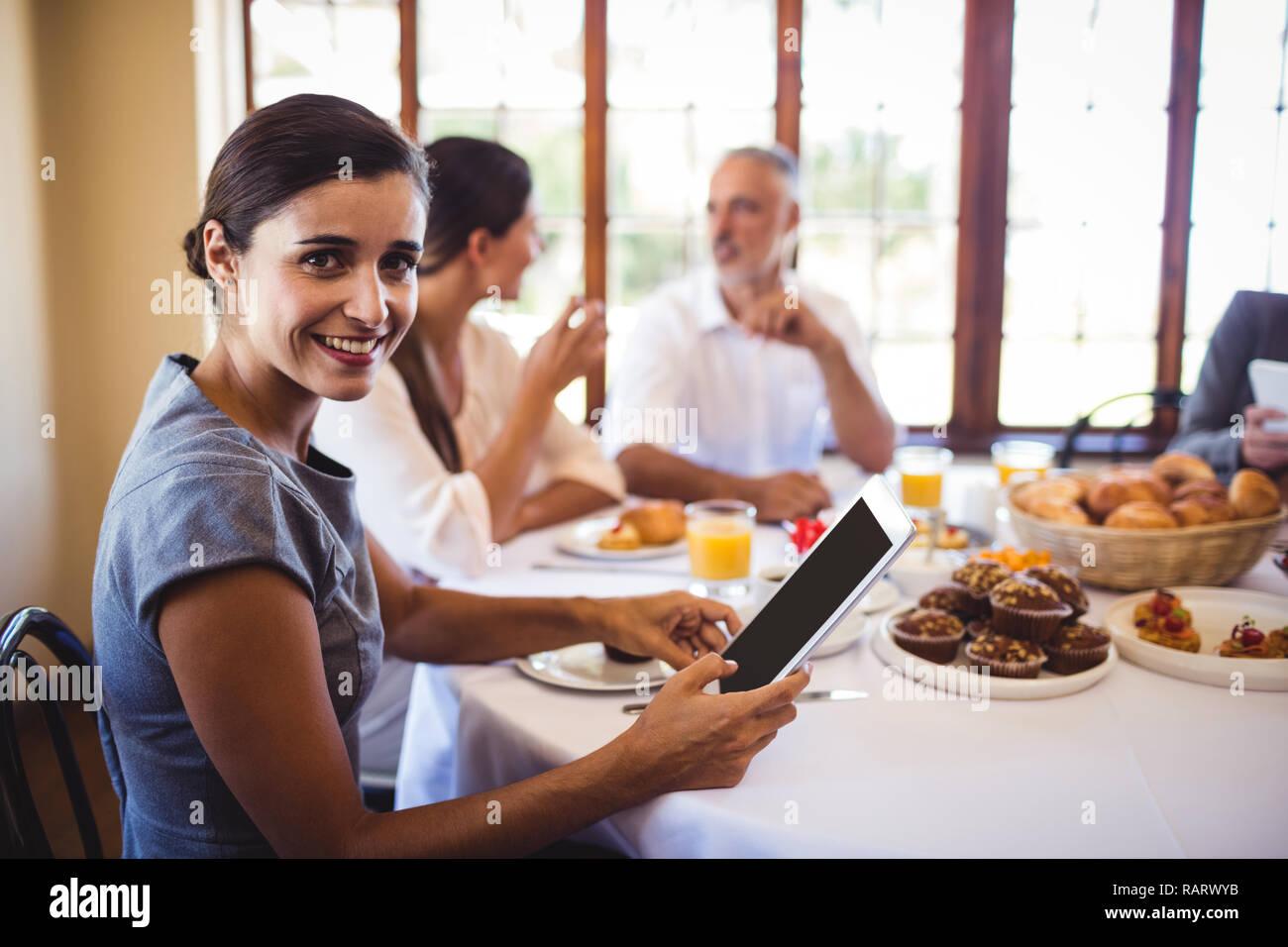Geschäftsfrau, die an der Kamera, während mit digitalen Tablet Stockfoto