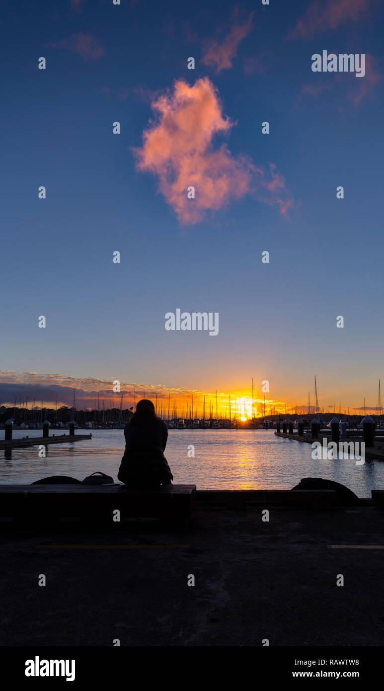 Eine Frau und einen warmen Sonnenuntergang über dem Hafen von Auckland in Neuseeland Stockbild
