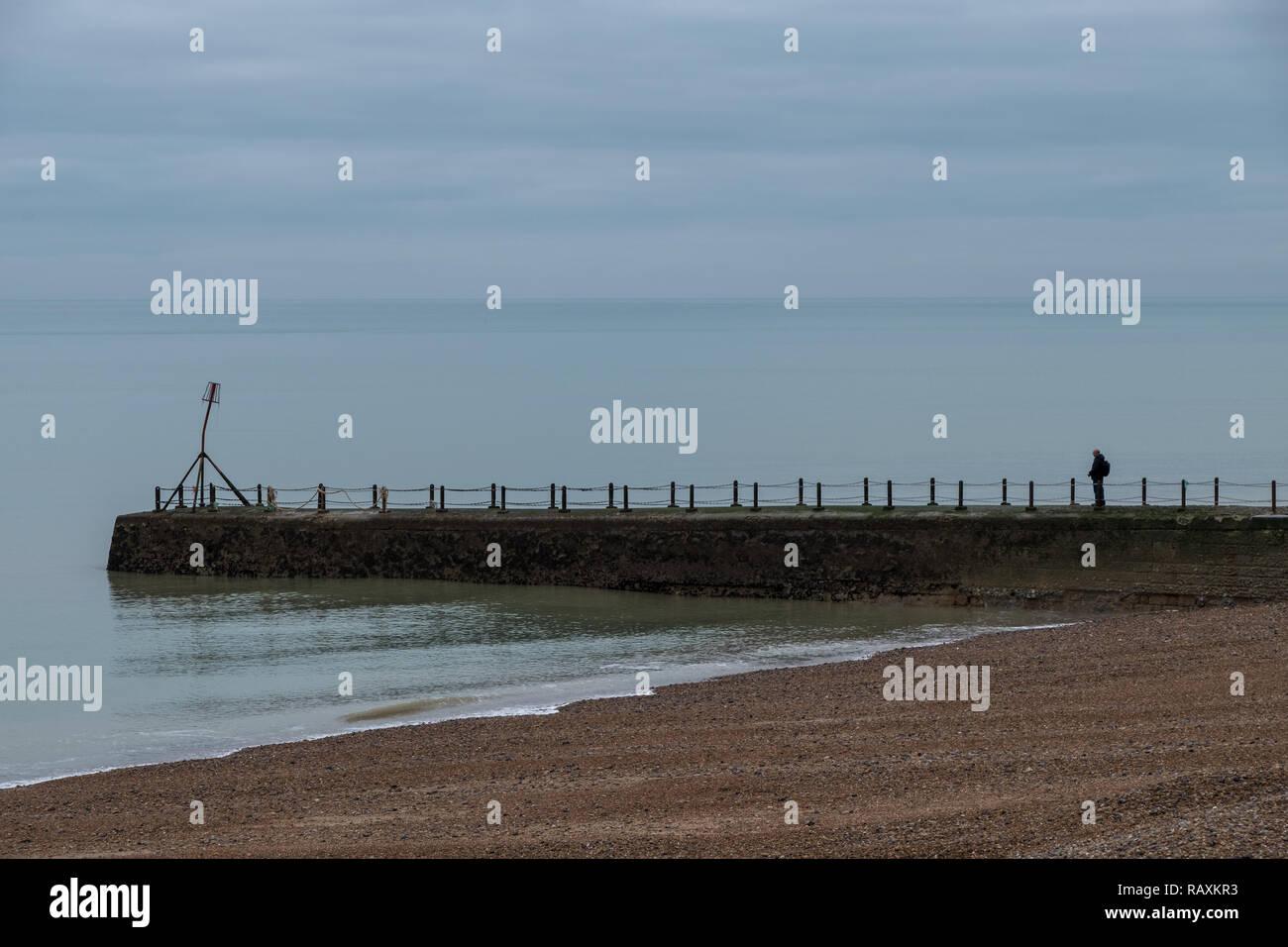 Einsame Mann steht auf der Mole an der Küste in Hove, Sussex, UK. In einem kalten Winter fotografiert. Stockbild