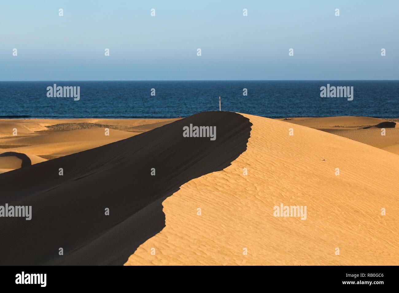 Lange Schatten auf Cascading Sanddünen in der Wüste mit Blick auf das Meer/See bei Sonnenuntergang (Dunas de Maspalomas, Gran Canaria, Spanien, Europa) Stockfoto