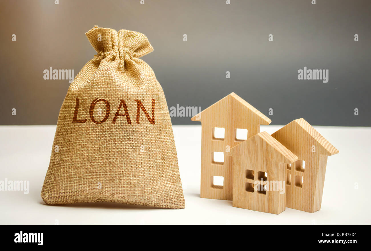 Holzhäuser und einen Beutel mit dem Wort Darlehen Kauf