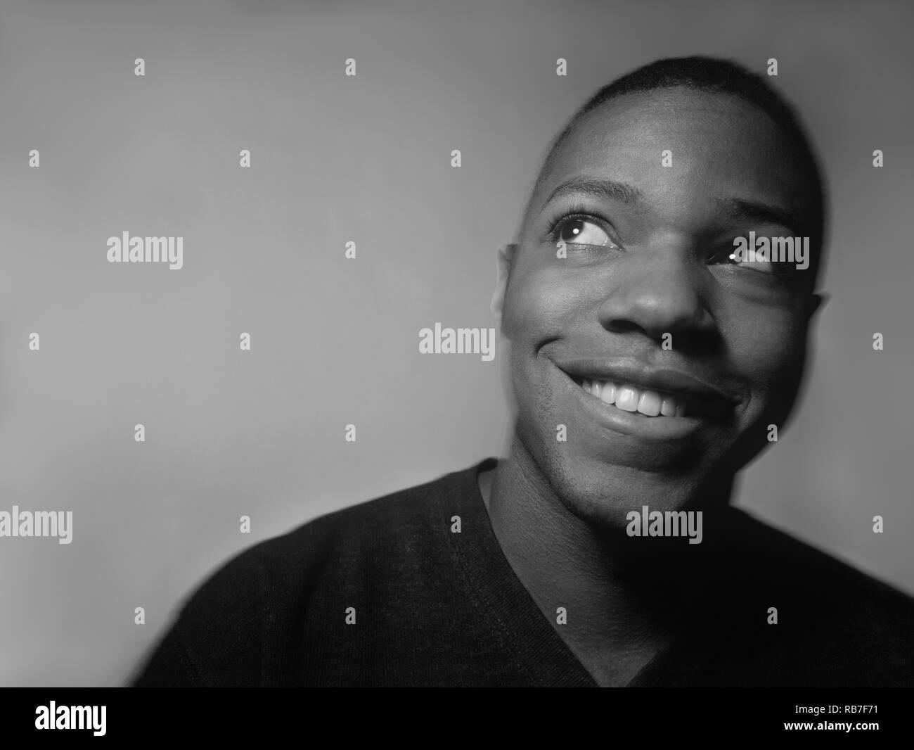 Schwarzer Mann lächelnd und Denken über etwas in seinem Geist und seinem Blick nach rechts Stockbild
