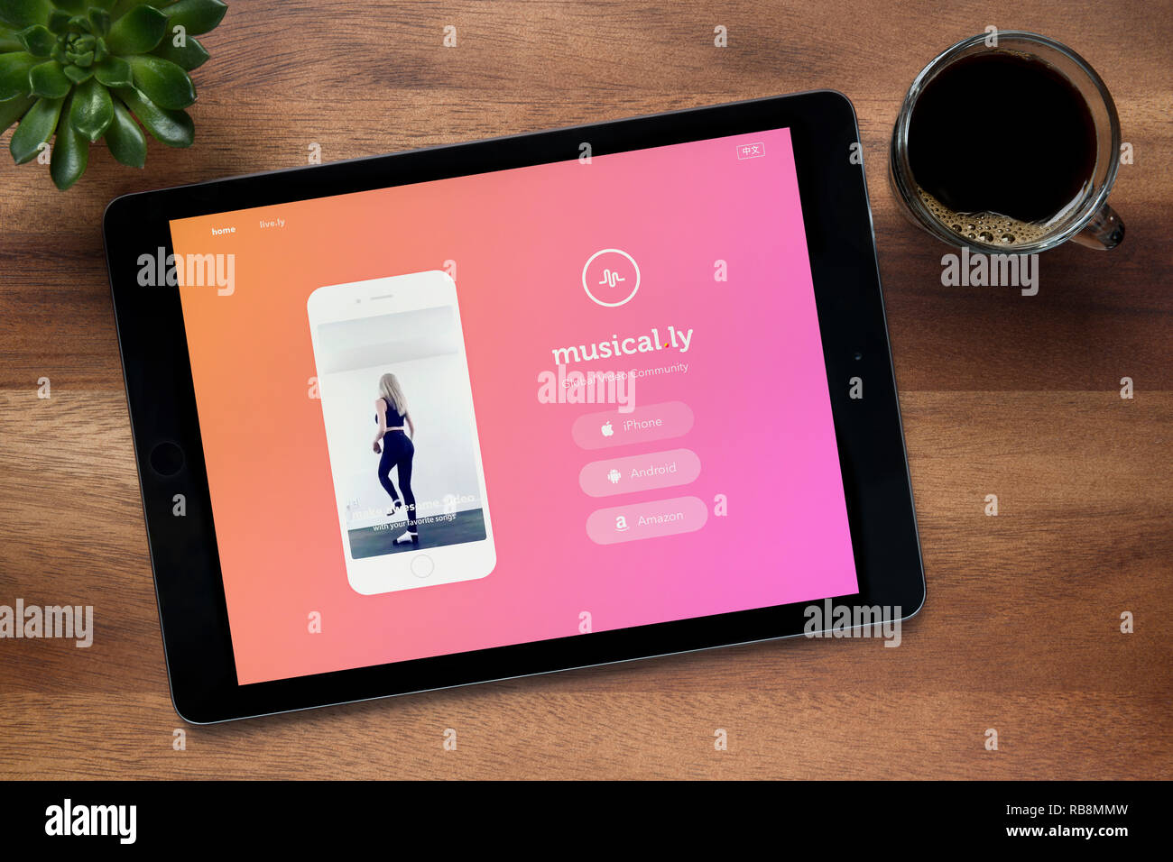 Die Website von musikalischen.ly ist, auf einem iPad Tablet gesehen, auf einer hölzernen Tisch zusammen mit einem Espresso und einem Haus Anlage (nur redaktionelle Nutzung). Stockbild