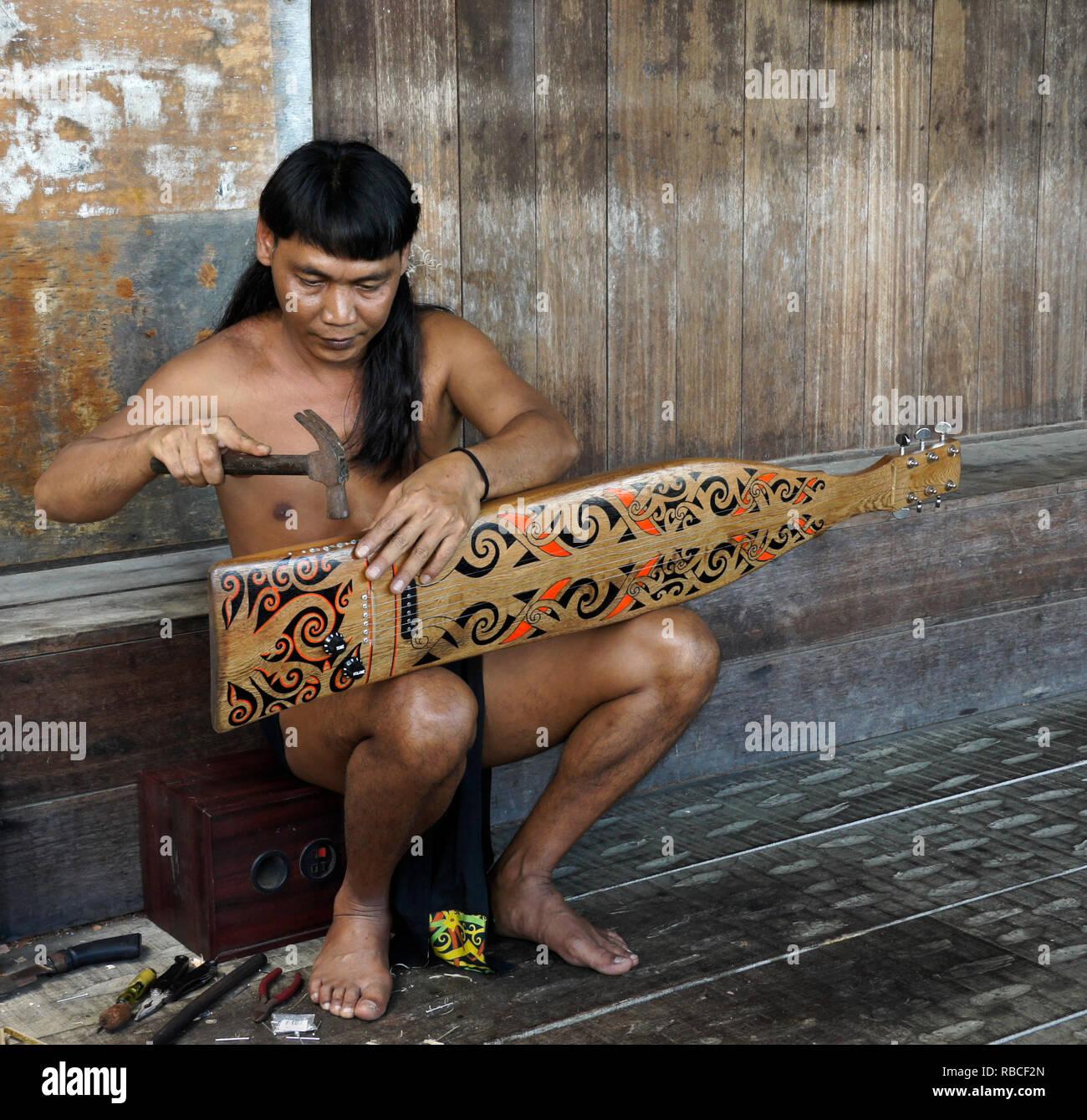 Orang Lake tribal Mann einen Sape (traditionelle Laute), Sarawak Cultural Village, Kuching, Sarawak (Borneo), Malaysia Stockbild