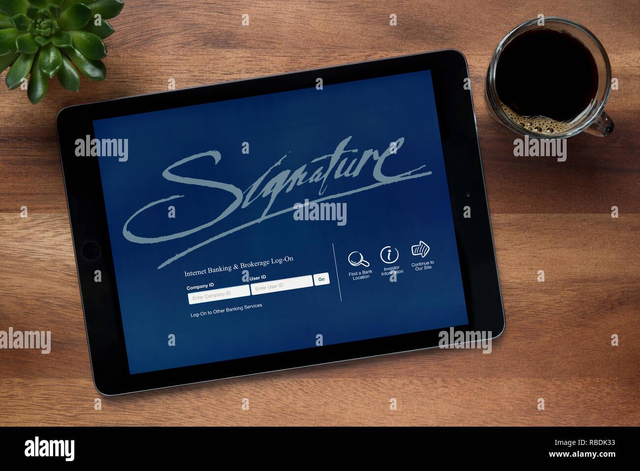 Die Website von Signatur Internet Banking ist auf einem iPad Tablet gesehen, ruht auf einem Holztisch (nur redaktionelle Nutzung). Stockbild