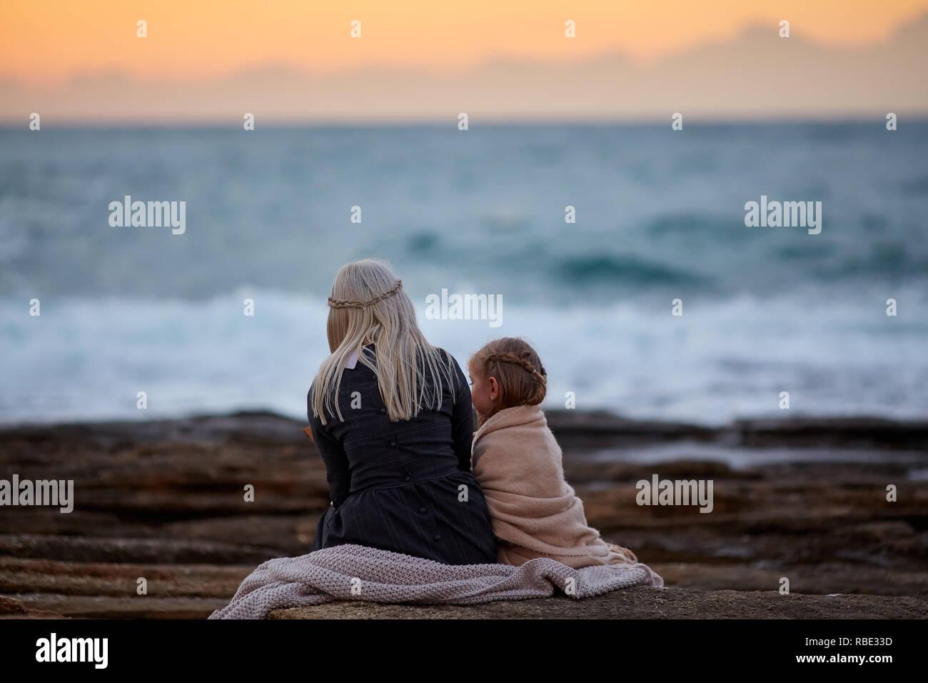Frau mit Mädchen kuscheln sich Seashore Stockfoto