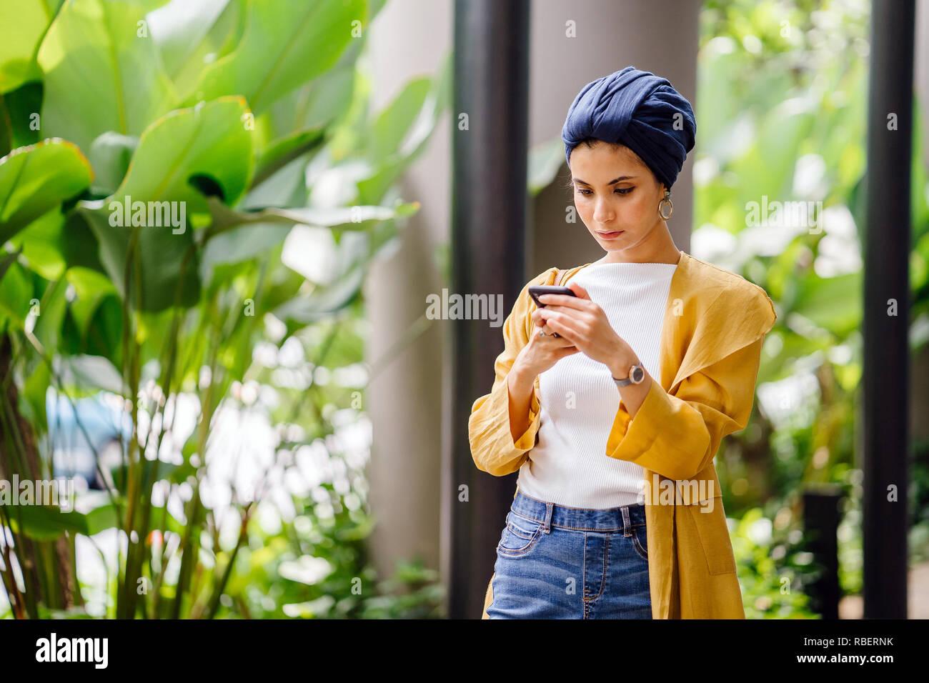 Ein naher Osten arabische Frau mit Kopftuch ist SMS und Messaging auf Ihrem Smartphone auf einer Straße in der Stadt während des Tages. Stockbild
