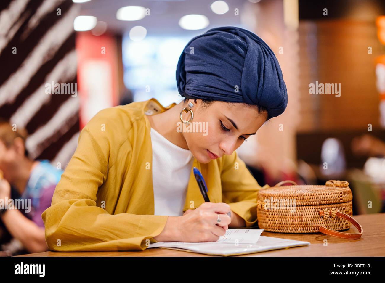 Porträt eines schönen und eleganten im Nahen und Mittleren Osten Frau schreiben in ihrer Zeitschrift notebook. Sie trägt einen blauen Turban hijab Kopftuch. Stockbild