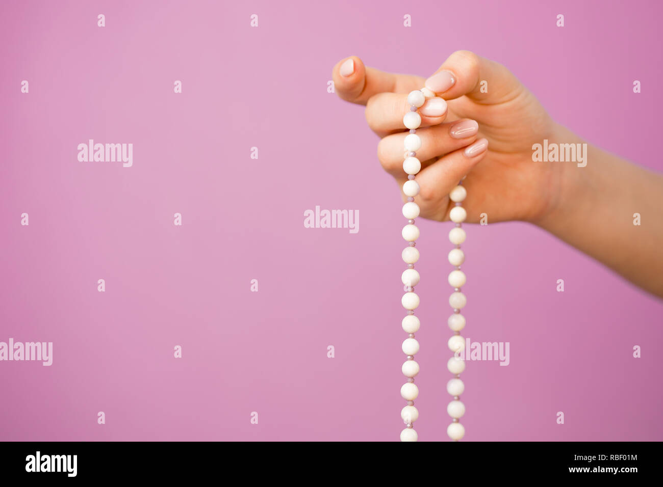 Frau, Hand leuchtet, zählt Malas, Stränge Edelsteine Perlen für das Halten zählen während mantra Meditationen auf rosa Hintergrund verwendet Stockfoto