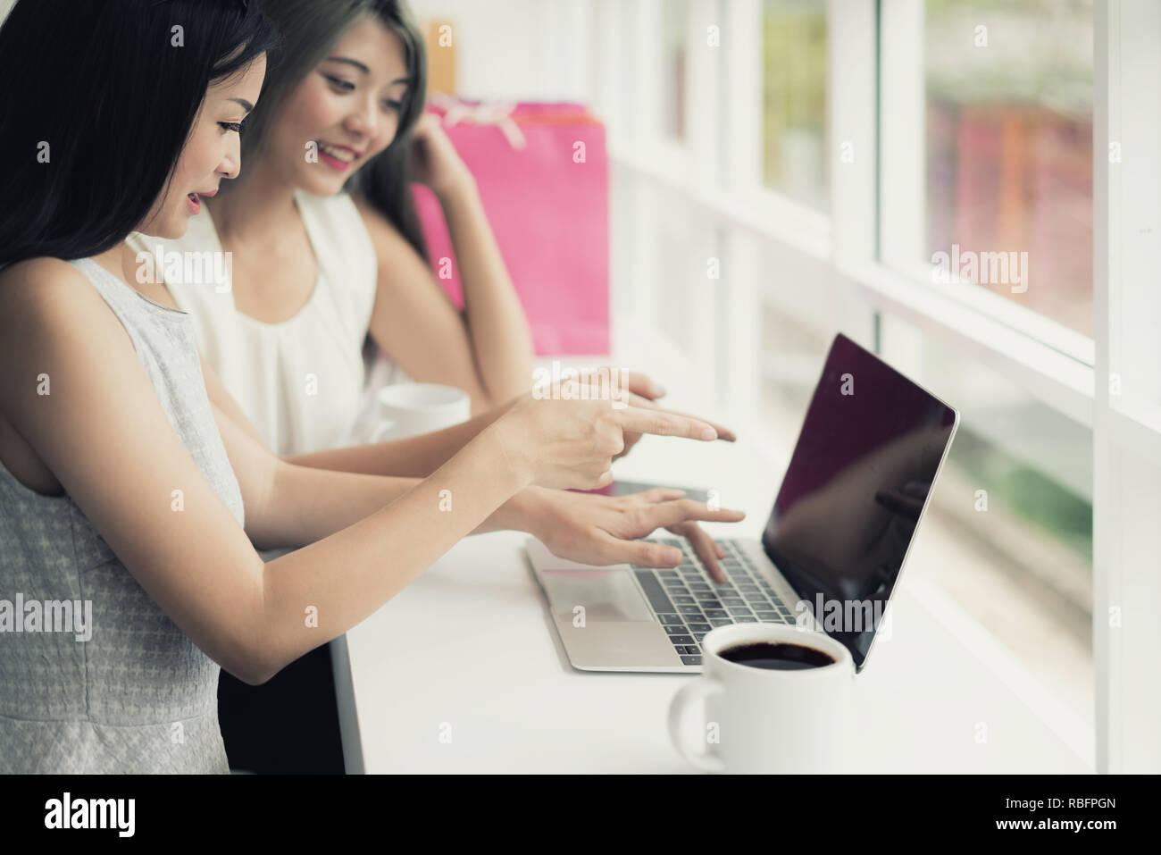 76c17902f81d82 Zwei asiatische Frau zusammen Einkaufen mit Tüten in der Hand und mit  Laptop, Shopping online Konzept.