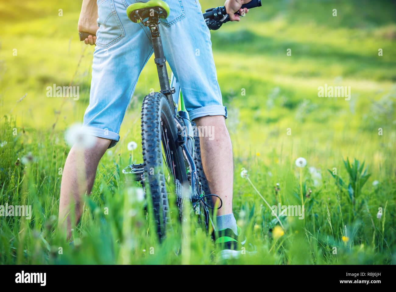 Radfahrer auf einem Green Mountain Bike in den Wald reiten auf dem Gras. Unter- und Rückseite. Das Konzept der aktiven und extremen Lebensstil Stockfoto