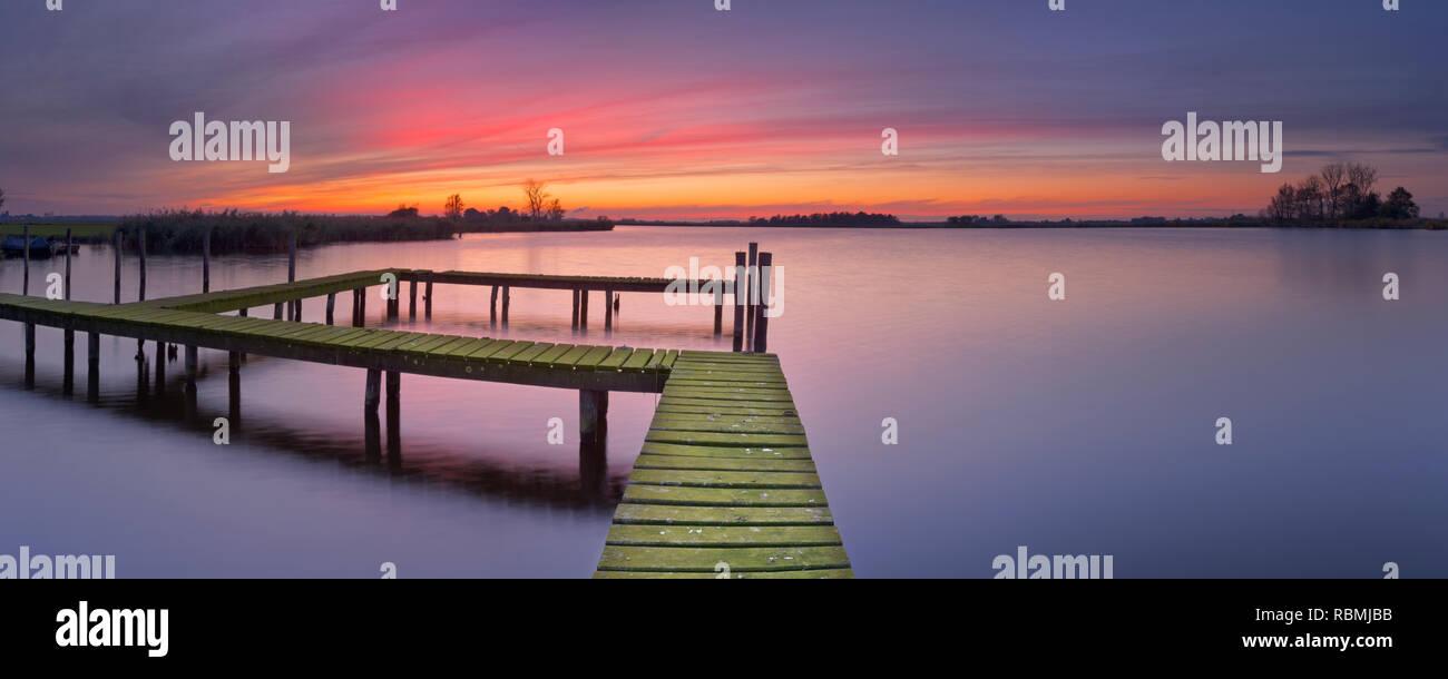 Eine alte Steg am See in den Niederlanden, bei Sonnenuntergang fotografiert. Stockbild