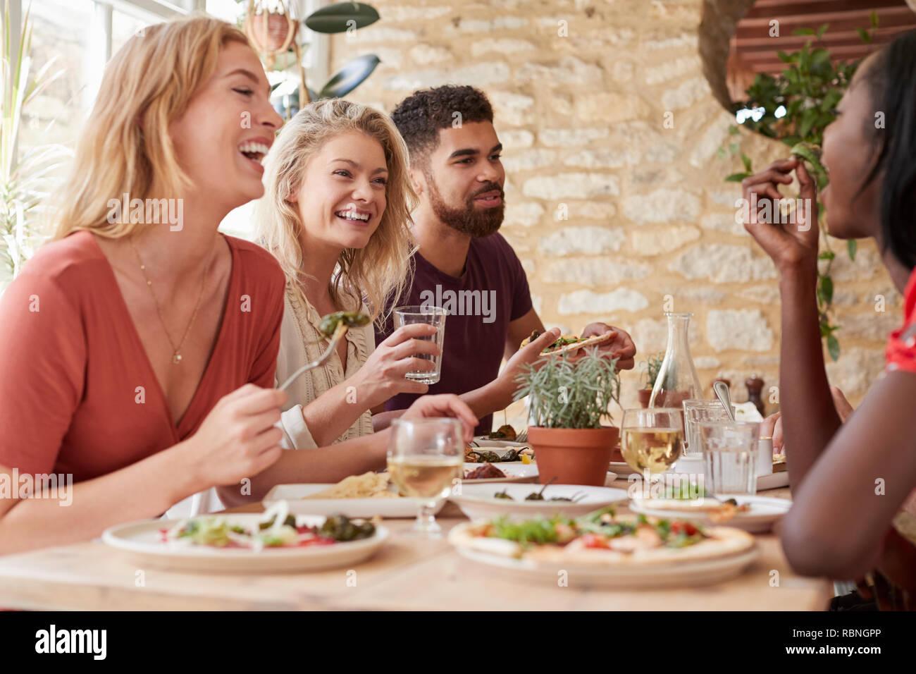 vier junge erwachsene freunde essen in einem restaurant. Black Bedroom Furniture Sets. Home Design Ideas