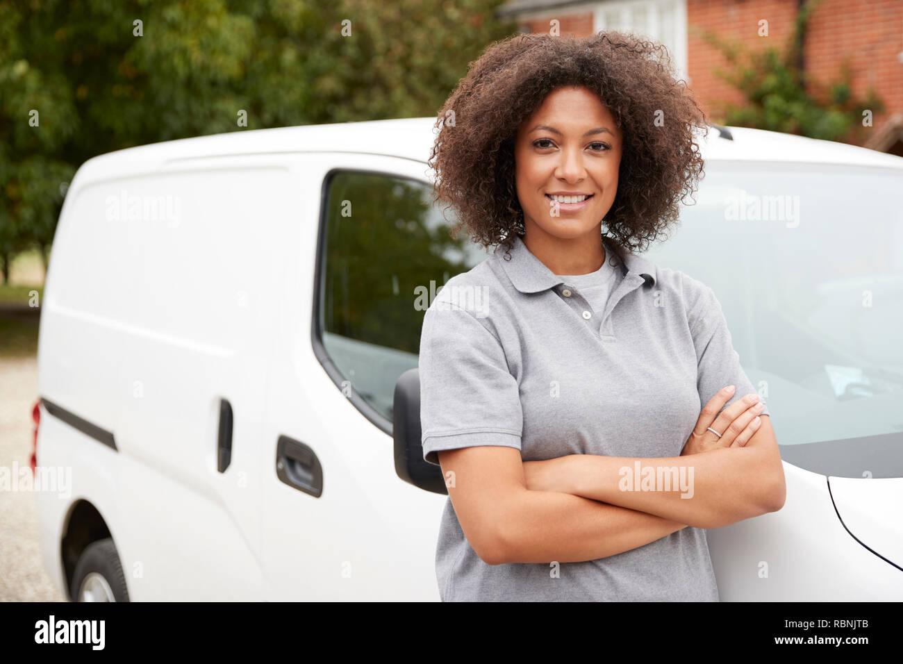 Junge schwarze weibliche tradesperson neben Ihrem weißen Van mit verschränkten Armen stand, in der Nähe Stockfoto
