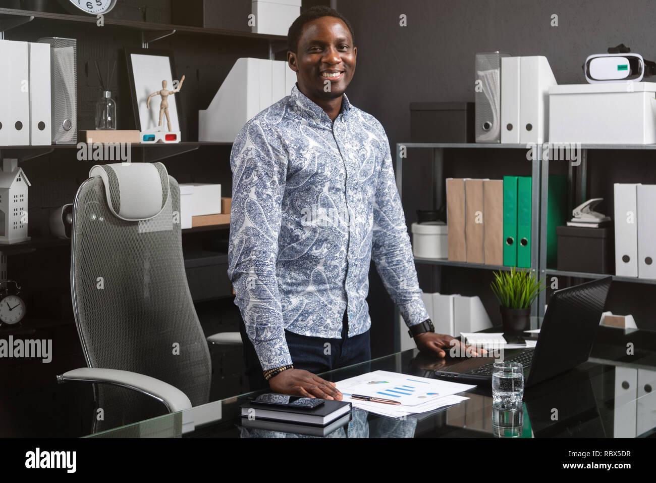 Portrait von drei Viertel lang junge schwarze Unternehmer stehen in der Nähe des Schreibtisch im Büro Stockbild