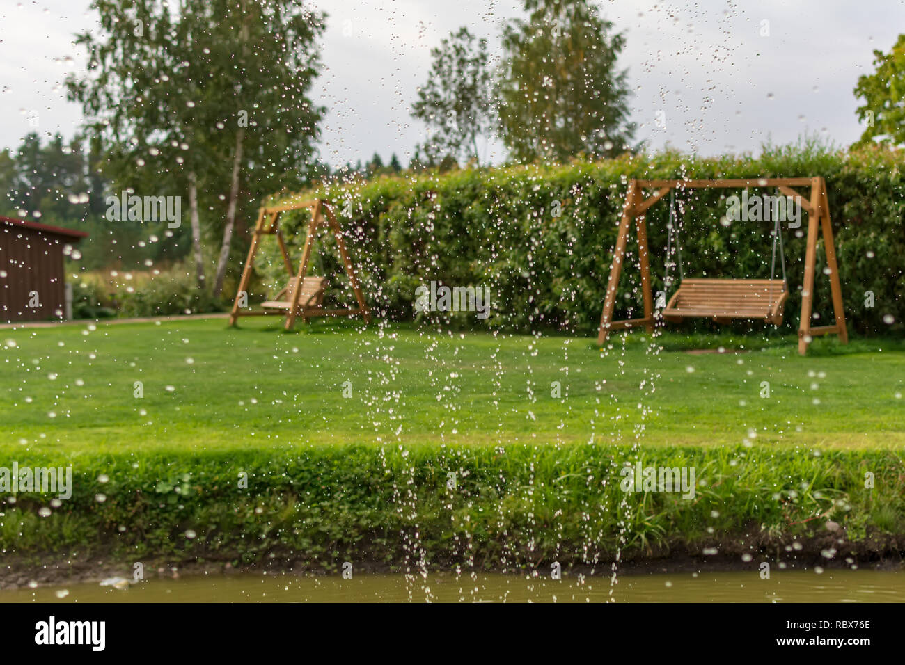 Zwei Holz- swing Bänke im Garten mit Wassertropfen im Vordergrund ...