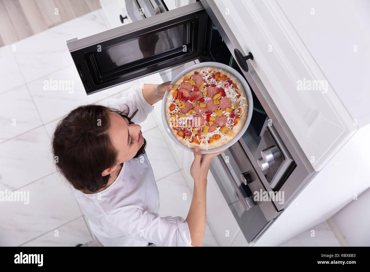 Close Up Eine Gluckliche Frau Backen Pizza In Der Mikrowelle