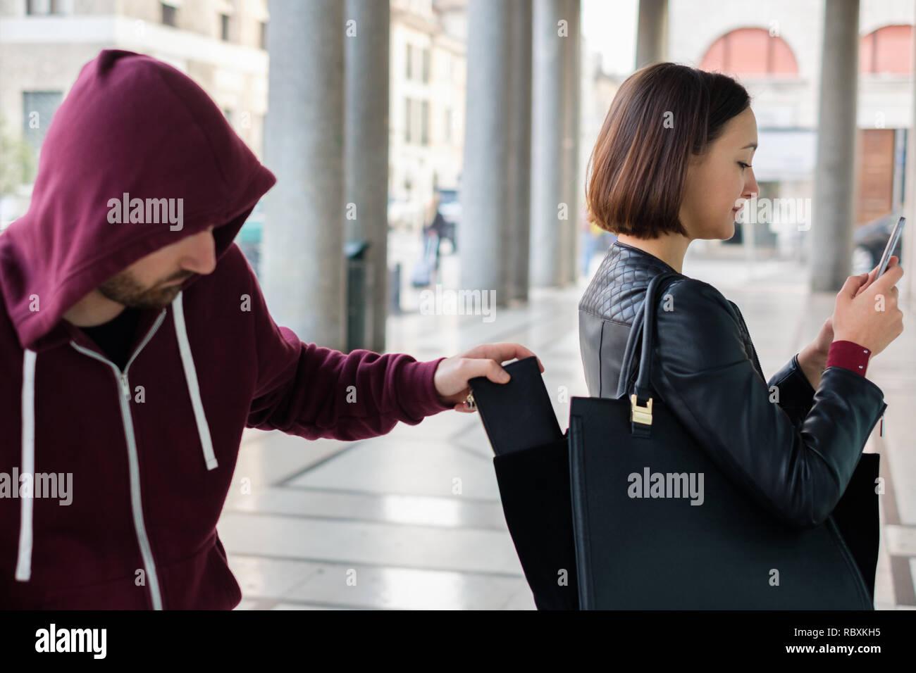 ec822636f27d2 Einbrecher stehlen Geld Portemonnaie aus der Handtasche einer zerstreuten  Frau Stockbild