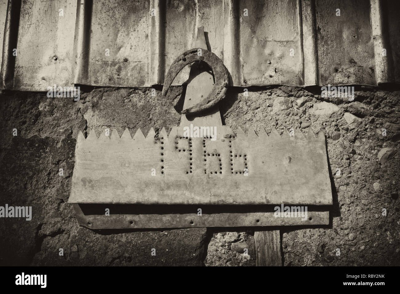 Altes rostiges Hufeisen hängen auf der Steinmauer von Bauernhaus. Alte Metall Hufeisen auf Stein Textur. Symbol für Glück. Armenien Stockbild