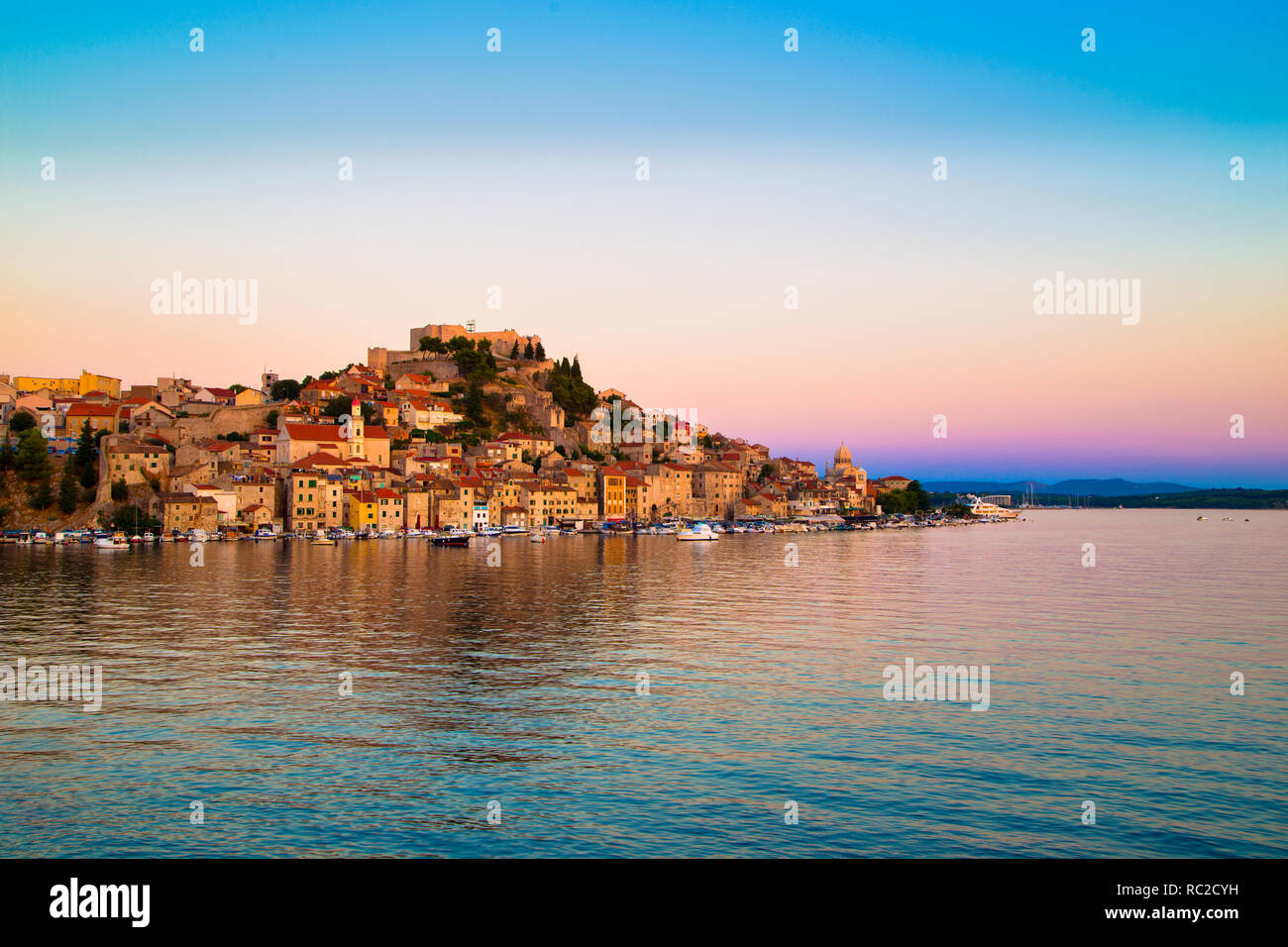 Historische Gebäude und kleine Boote im Hafen von Sibenik, Kroatien Stockbild