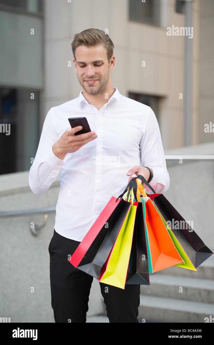 Unternehmer nutzen Sie die Anwendung. Der Mensch trägt Einkaufstaschen während Halten Sie Telefon im städtischen Hintergrund. Erfolgreicher Geschäftsmann online einkaufen. Beschäftigte Leute schätzen Online Service. Online einkaufen. Stockbild