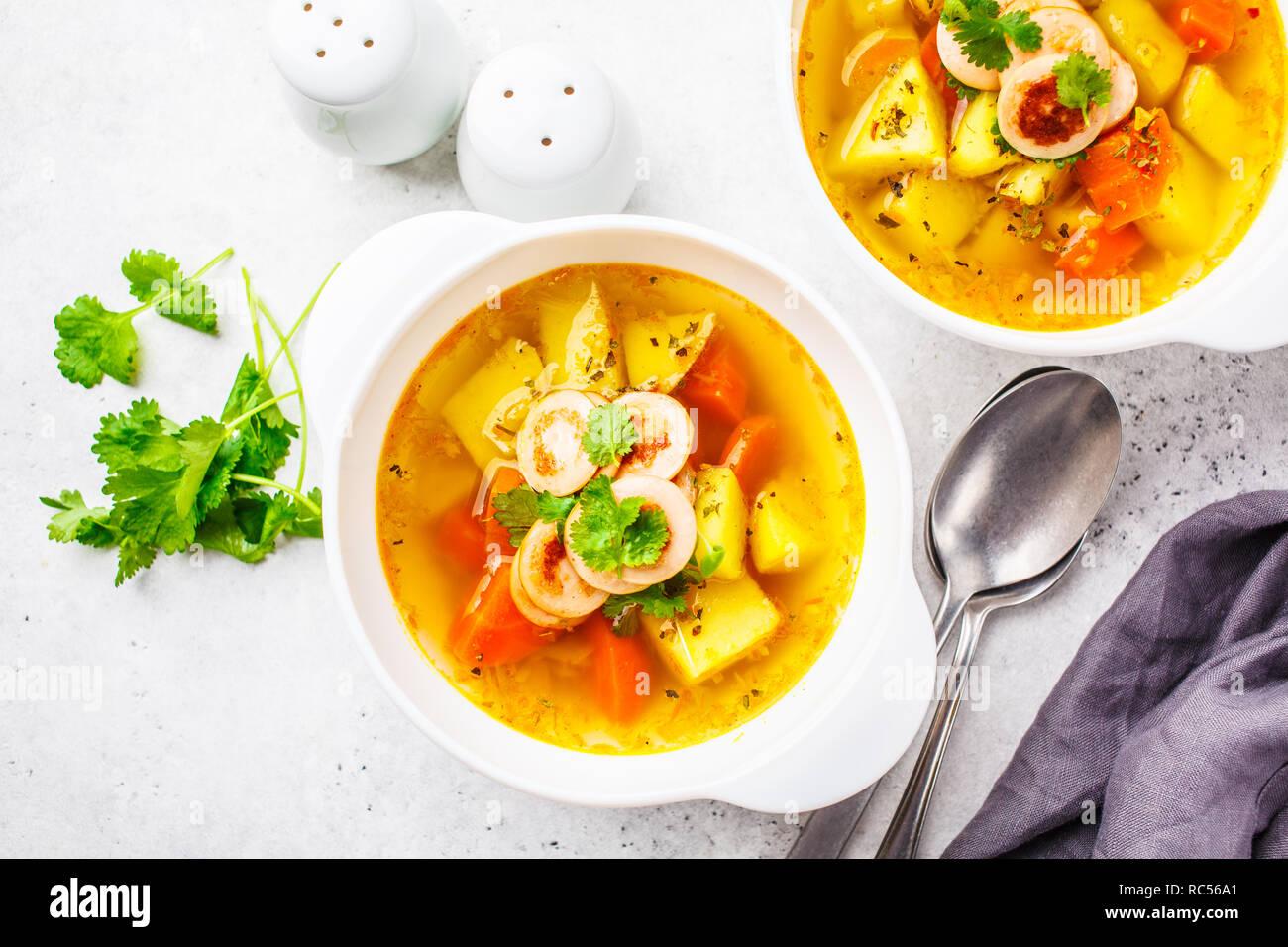 Deutsche Kartoffelsuppe mit Würstchen und Gemüse in weißen ...